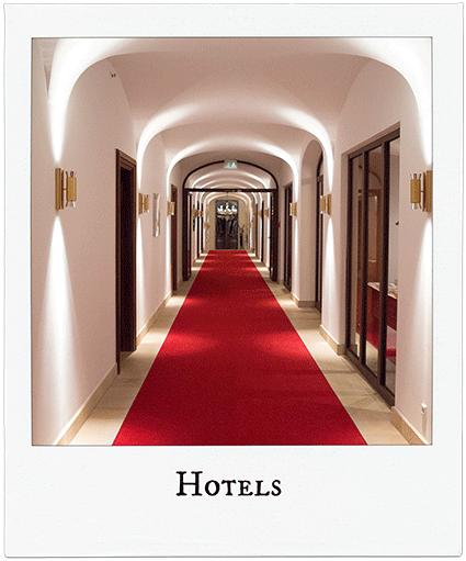 Langer Hotelflur mit rotem Teppich.