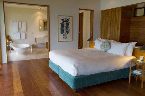 Blick auf Bett und Bad des Qualia Resort.