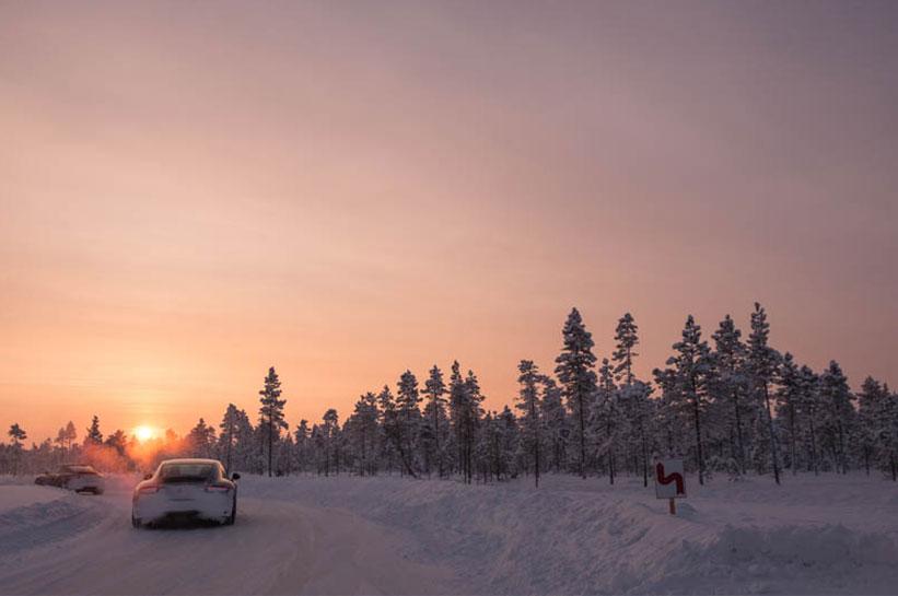 Porsche im Schnee fahren in den Sonnenuntergang.