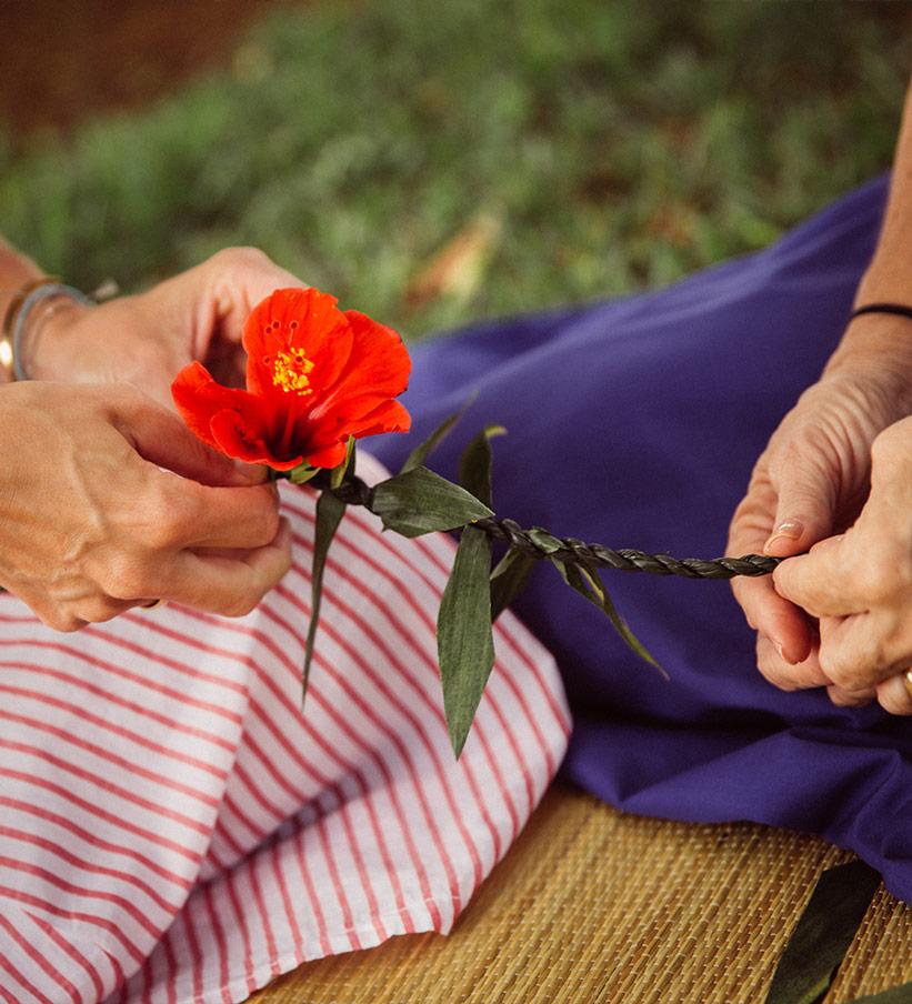 Traditionelle Blumenkette flechten auf Hawaii