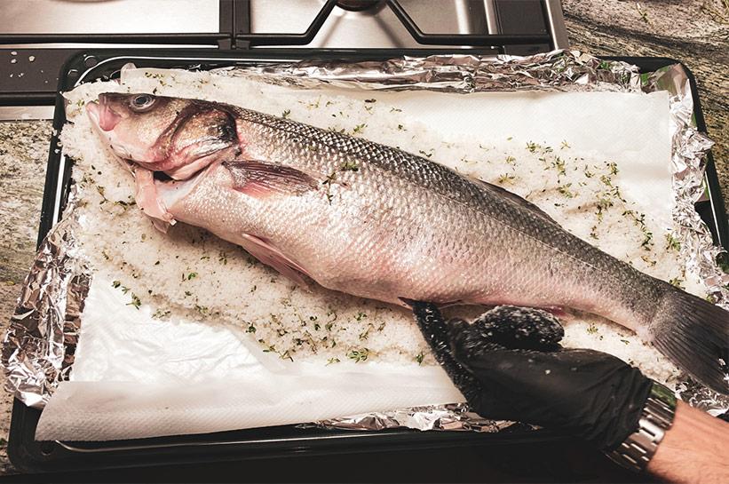 Fisch wird mit Kräutern gefüllt